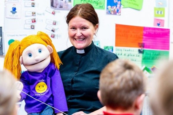 A Minister holding a puppet with a group of school children