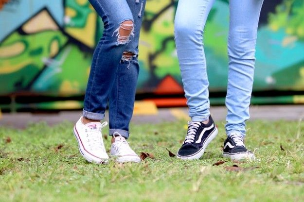 The legs of two people wearing jeans and trainers